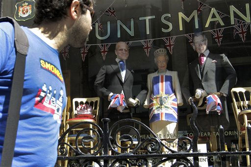 A man looks at a shop window displaying its wares with masks depicting Queen Elizabeth II, center, her husband Duke of Edinburgh, left, and her son Prince Charles to celebrate the forthcoming royal wedding of Prince William and Kate Middleton, Friday, April 22, 2011. Prince William and Kate Middleton are to marry at Westminster Abbey in London on April 29. &#40;AP Photo&#47;Sang Tan&#41; <span class=meta>(AP Photo&#47; Sang Tan)</span>