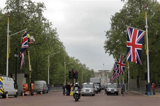 Workers put up a British flag, left, along the Mall, backdropped by Buckingham Palace, in London in preparation for the royal wedding, Tuesday, April 26, 2011. Prince William and Kate Middleton are to marry at Westminster Abbey in London on April 29. &#40;AP Photo&#47;Sang Tan&#41; <span class=meta>(AP Photo&#47; Sang Tan)</span>