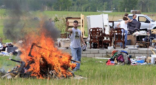 A man throws rubble into a bonfire as he helps to clean up at the home of Jay and Carla Arendal on Tuesday, April 26, 2011, after a tornado destroyed the Arendal&#39;s home in Vilonia, Ark. The couple was in the home during the storm and both survived. &#40;AP Photo&#47;Mark Humphrey&#41; <span class=meta>(AP Photo&#47; Mark Humphrey)</span>