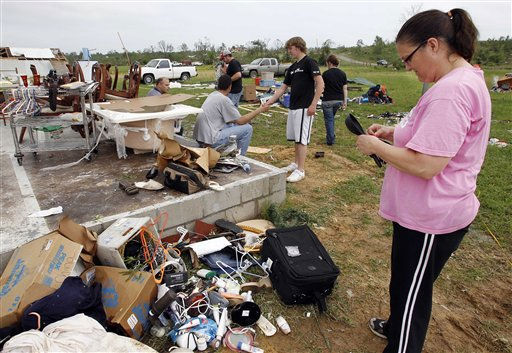 Carla Arendal looks at some jewelry she salvaged from her home on Tuesday, April 26, 2011, after a tornado destroyed the building in Vilonia, Ark. Arendal and her husband, Jay, were in the home during the storm and survived unhurt. &#40;AP Photo&#47;Mark Humphrey&#41; <span class=meta>(AP Photo&#47; Mark Humphrey)</span>