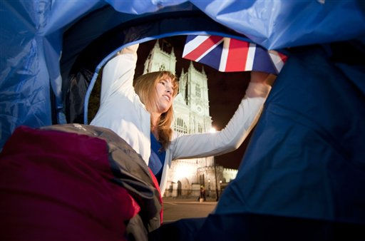 Diane Basilius from Grand Rapids, Mich., fixes a British flag outside of her new tent in front of Westminster Abbey in London, late Tuesday night, April 26, 2011. Basilius arrived from the U.S. for the Royal wedding and bought a tent spontaneously to camp outside the Abbey where Prince William and Kate Middleton are due to get married on Friday, April 29. &#40;AP Photo&#47;Gero Breloer&#41; <span class=meta>(AP Photo&#47; Gero Breloer)</span>