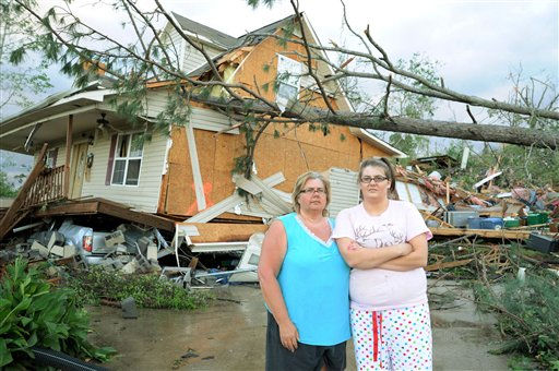 Diane and Ashley Guyton, victims of the tornado that ripped through Concord, Ala., pose for a photo in front of their house, Thursday, April 28, 2011. The gray truck, underneath the home, saved their lives. Diane and Ashley ran with their family to the basement when they heard the sound of the tornado and jumped into the truck as the house fell. &#40;AP Photo&#47;Wynter Byrd&#41; <span class=meta>(AP Photo&#47; Wynter Byrd)</span>