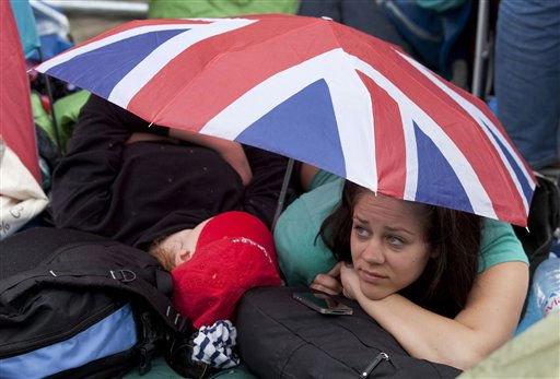 Royal enthusiasts use an umbrella to protect themselves from the sun as they sleep in front of Westminster Abbey in London, Thursday, April 28, 2011. Revelers are camping out outside the Abbey where Prince William and Kate Middleton are due to get married on Friday, April 29. &#40;AP Photo&#47;Gero Breloer&#41; <span class=meta>(AP Photo&#47; Gero Breloer)</span>