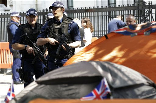 Armed police officers patrol pass the tents set up by royal supporters queuing to see the royal wedding outside Westminster Abbey in London, Thursday, April 28, 2011. Prince William and Kate Middleton are to marry in Westminster Abbey on Friday, April 29. &#40;AP Photo&#47;Sang Tan&#41; <span class=meta>(AP Photo&#47; Sang Tan)</span>