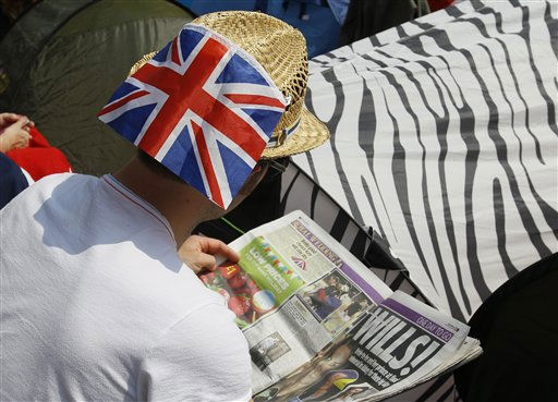 A royal fan reads about the Royals in a newspaper as he sits on the pavement near Westminster Abbey in London, Thursday, April 28, 2011. Royal  enthusiasts are camping out on the pavement to reserve a spot to watch Prince William and Kate Middleton as they arrive to marry in Westminster Abbey on Friday, April 29. &#40;AP Photo&#47;Kirsty Wigglesworth&#41; <span class=meta>(AP Photo&#47; Kirsty Wigglesworth)</span>