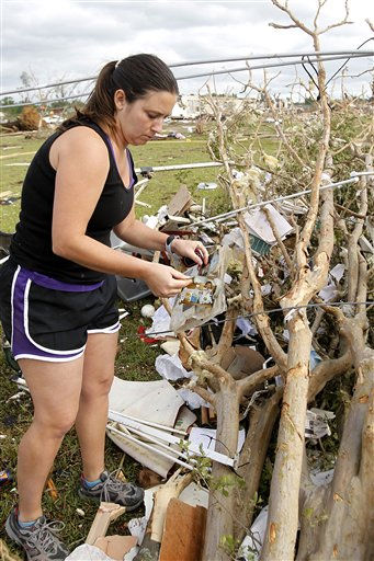 "<div class=""meta ""><span class=""caption-text "">Mandy Coolidge collects photos from the debris after a tornado the day before hit Pleasant Grove just west of downtown Birmingham, Ala., on Thursday, April 28, 2011. (AP Photo/Butch Dill) (AP Photo/ Butch Dill)</span></div>"