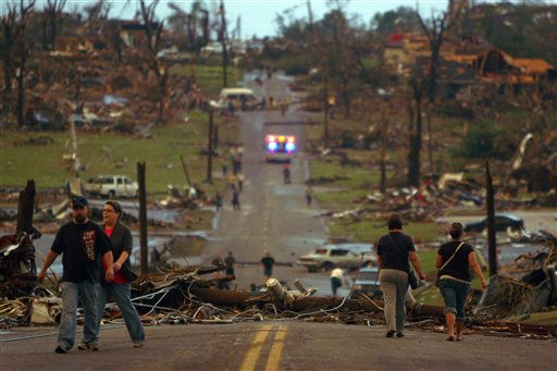 People walk down a street lined with destroyed homes in Joplin, Mo., Sunday, May 22, 2011. A large tornado moved through much of the city, damaging a hospital and hundreds of homes and businesses. &#40;AP Photo&#47;Mark Schiefelbein&#41; <span class=meta>(AP Photo&#47; Mark Schiefelbein)</span>