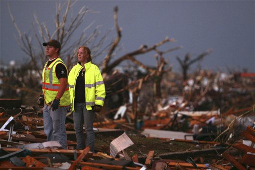 William Jackson, left, and Ashley Martin, volunteer firefighters from Oklahoma, survey the wreckage of destroyed homes in Joplin, Mo., Sunday, May 22, 2011. A large tornado moved through much of the city, damaging a hospital and hundreds of homes and businesses. &#40;AP Photo&#47;Mark Schiefelbein&#41; <span class=meta>(AP Photo&#47; Mark Schiefelbein)</span>