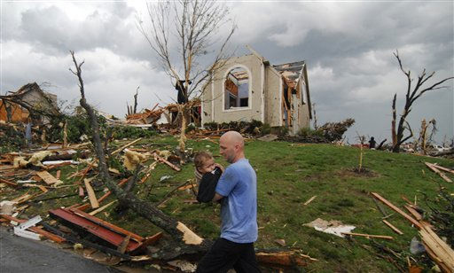 A man carries a young boy who was rescued after being trapped in his home after a tornado hit Joplin, Mo. on Sunday evening, May 22, 2011. The tornado tore a path a mile wide and four miles long destroying homes and businesses. &#40;AP Photo&#47;Mike Gullett&#41; <span class=meta>(AP Photo&#47; Mike Gullett)</span>
