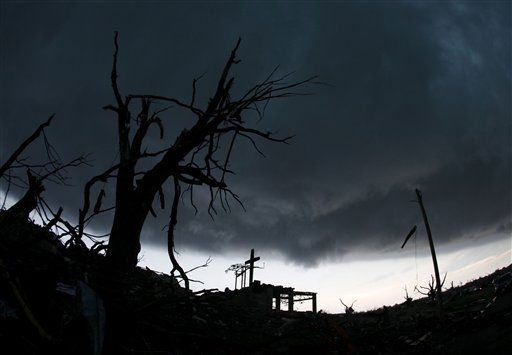 "<div class=""meta ""><span class=""caption-text "">A cross stands atop a church that was severely damaged by a tornado in Joplin, Mo., as a severe storm passes overhead Monday, May 23, 2011. A large tornado moved through much of the city Sunday, damaging a hospital, hundreds of homes and businesses and killing at least 89 people. (AP Photo/Charlie Riedel) (AP Photo/ Charlie Riedel)</span></div>"