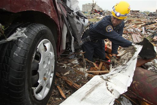 Rescue specialist Kris Tate of the Springfield, Mo., Fire Department digs under a destroyed vehicle at a home near the St. John&#39;s Regional Medical Center in Joplin, Mo., Monday, May 23, 2011. A destructive tornado moved through the city on Sunday evening, killing at least 89 people and injuring hundreds more. &#40;AP Photo&#47;Mark Schiefelbein&#41; <span class=meta>(AP Photo&#47; Mark Schiefelbein)</span>