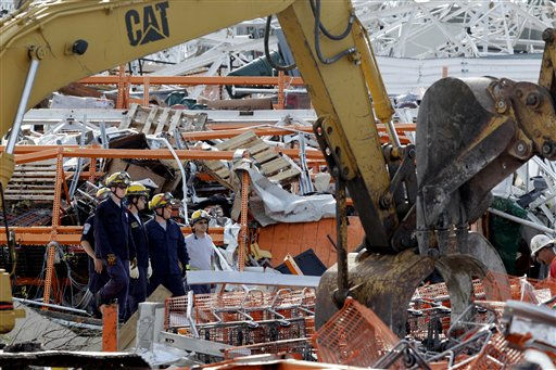 Members of Missouri Task Force One search-and-rescue team stand by as heavy equipment moves debris from a tornado-damaged Home Depot store Tuesday, May 24, 2011, in Joplin , Mo. A large tornado moved through much of the city Sunday, damaging a hospital and hundreds of homes and businesses. &#40;AP Photo&#47;Jeff Roberson&#41; <span class=meta>(AP Photo&#47; Jeff Roberson)</span>