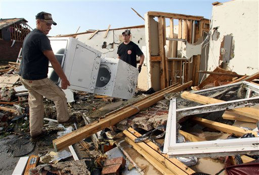 Greg Beeching, left, of Carl Junction, Mo., and his son Brian Beeching of Joplin, Mo., move a washer and dryer out of a relative&#39;s damaged apartment in Joplin, Tuesday, May 24, 2011. At least 116 people were killed and hundreds more injured when a tornado cut a destructive path through Joplin on Sunday evening. &#40;AP Photo&#47;Mark Schiefelbein&#41; <span class=meta>(AP Photo&#47; Mark Schiefelbein)</span>