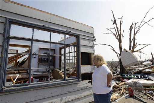 "<div class=""meta image-caption""><div class=""origin-logo origin-image ""><span></span></div><span class=""caption-text"">Linda Dinwiddie stands outside a tornado-damaged house belonging to her nephew Tuesday, May 24, 2011, in Joplin , Mo. A large tornado moved through much of the city Sunday, damaging a hospital and hundreds of homes and businesses. (AP Photo/Jeff Roberson) (AP Photo/ Jeff Roberson)</span></div>"
