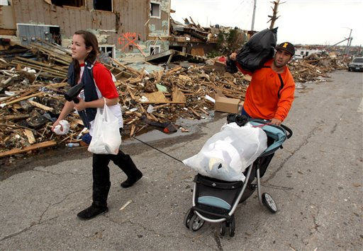 Missouri Southern State University students Jessi Yates of Phillipsburg, Kan., left, and Grant Conrad of Lafayette, La., use a broken stroller to carry some of the belongings they salvaged from Conrad&#39;s apartment as they walk down 20th Street in Joplin, Mo., Tuesday, May 24, 2011. At least 116 people were killed and hundreds more injured when a tornado cut a destructive path through Joplin on Sunday evening. &#40;AP Photo&#47;Mark Schiefelbein&#41; <span class=meta>(AP Photo&#47; Mark Schiefelbein)</span>