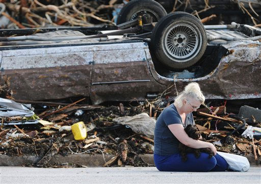 "<div class=""meta ""><span class=""caption-text "">Heidi Ackerson, sits in the street near her home with one of her dogs on Tuesday, May 24, 2011, in Joplin, Mo. Ackerson and her husband, Darrell, hid in a closet in their home during the tornado that hit their home on Sunday. They are heading to a shelter with only their dogs and the clothes on their backs. (AP Photo/Mike Gullett) (AP Photo/ Mike Gullett)</span></div>"