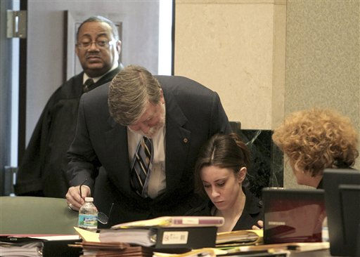 "<div class=""meta image-caption""><div class=""origin-logo origin-image ""><span></span></div><span class=""caption-text"">Judge Belvin Perry, rear, enters the court behind the defense table where attorney Cheney Mason, standing, defendant Casey Anthony and attorney Dorothy Clay Sims, right, talk during Anthony's trial at the Orange County Courthouse, Friday, May 27, 2011 in Orlando, Fla. Anthony, 25, has pleaded not guilty to first-degree murder of her daughter, 2-year-old Caylee Anthony, in the summer of 2008. If convicted, she could be sentenced to death. (AP Photo/Red Huber, Pool) (AP Photo/ Red Huber)</span></div>"