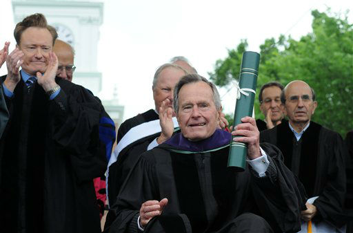 In this June 12, 2011 photo, former President George H.W. Bush holds an honorary Doctor of Laws degree from Dartmouth College presented to him during commencement exercises at the College in Hanover, N.H. Talk show host Conan O&#39;Brien looks on, at left. <span class=meta>(AP photo)</span>