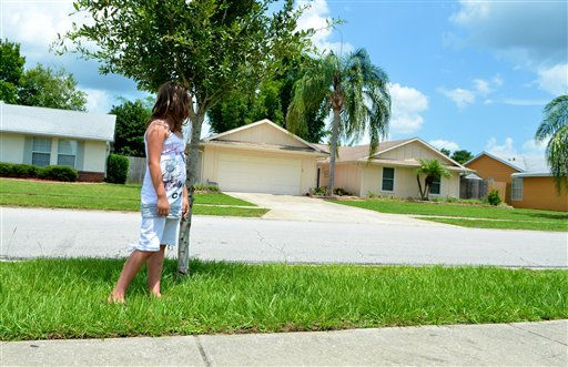 Olivia Colonna, 7, visiting from Toronto, Canada, looks back at the pale yellow house of George and Cindy Anthony moments after Casey Anthony was found not guilty in the death of her daughter, Orlando, Fla., Tuesday, July 5, 2011. (AP Photo/Roberto Gonzalez)