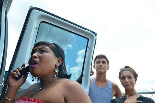 Down the street of the Anthony family home, Tiana McLeod (from left) Aaron Kaser, and Chelsea Rodriguez hear the news and react to the verdict of not guilty of murder being read in the case against Casey Anthony, Orlando, Fla., Tuesday, July 5, 2011. (AP Photo/Roberto Gonzalez)