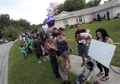 "<div class=""meta ""><span class=""caption-text "">A group of neighbors and visitors stand across the street from the George and Cindy Anthony residence as most express their disagreement with the Casey Anthony verdict in Orlando, Fla., Tuesday, July 5, 2011. Casey Anthony was found not guilty of first-degree murder, aggravated manslaughter and aggravated child abuse. (AP Photo/Alan Diaz) (AP Photo/ Alan Diaz)</span></div>"
