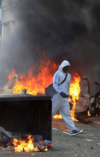 A masked youth walks by burning garbage bins set on fire by rioters in Hackney, east London, Monday, Aug. 8, 2011. Violence and looting spread across some of London&#39;s most impoverished neighborhoods on Monday, with youths setting fire to shops and vehicles, during a third day of rioting in the city that will host next summer&#39;s Olympic Games. &#40;AP Photo&#47;Lefteris Pitarakis&#41; <span class=meta>(AP Photo&#47; Lefteris Pitarakis)</span>