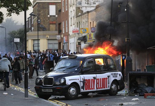 "<div class=""meta image-caption""><div class=""origin-logo origin-image ""><span></span></div><span class=""caption-text"">A car, behind the taxi, burns after it was set on fire by rioters in Hackney, east London, Monday Aug. 8, 2011. Youths set fire to shops and vehicles in a host of areas of London _ which will host next summer's Olympic Games _ and clashed with police in the nation's central city of Birmingham, as authorities struggled to halt groups of rampaging young people. (AP Photo/Lefteris Pitarakis) (AP Photo/ Lefteris Pitarakis)</span></div>"