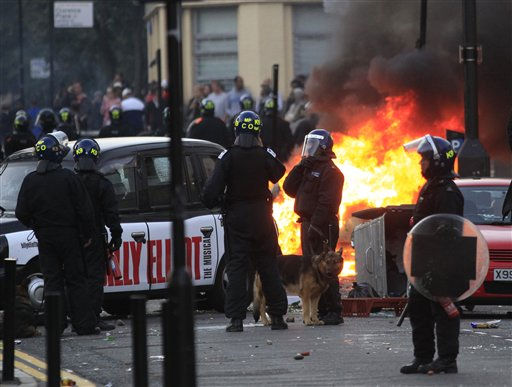 "<div class=""meta ""><span class=""caption-text "">British police officers stand around  as a car, background, burns after it was set on fire by rioters in Hackney, east London, Monday Aug. 8, 2011. Youths set fire to shops and vehicles in a host of areas of London _ which will host next summer's Olympic Games _ and clashed with police in the nation's central city of Birmingham, as authorities struggled to halt groups of rampaging young people.  (AP Photo/Lefteris Pitarakis) (AP Photo/ Lefteris Pitarakis)</span></div>"