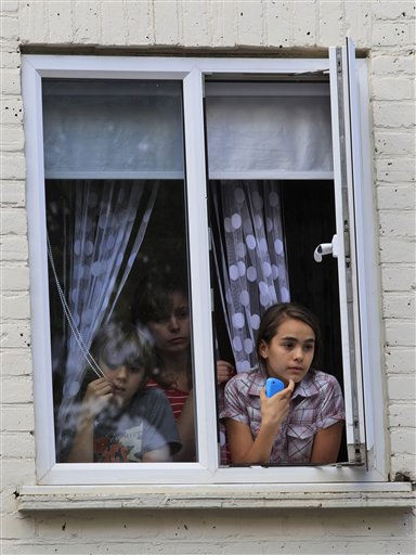 People watch from their window during riots in Hackney, east London, Monday Aug. 8, 2011. Youths set fire to shops and vehicles in a host of areas of London _ which will host next summer&#39;s Olympic Games _ and clashed with police in the nation&#39;s central city of Birmingham, as authorities struggled to halt groups of rampaging young people. &#40;AP Photo&#47;Lefteris Pitarakis&#41; <span class=meta>(AP Photo&#47; Lefteris Pitarakis)</span>