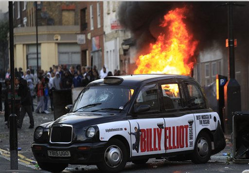 A car, behind the taxi, burns after it was set on fire by rioters in Hackney, east London, Monday Aug. 8, 2011. Youths set fire to shops and vehicles in a host of areas of London _ which will host next summer&#39;s Olympic Games _ and clashed with police in the nation&#39;s central city of Birmingham, as authorities struggled to halt groups of rampaging young people.  &#40;AP Photo&#47;Lefteris Pitarakis&#41; <span class=meta>(AP Photo&#47; Lefteris Pitarakis)</span>