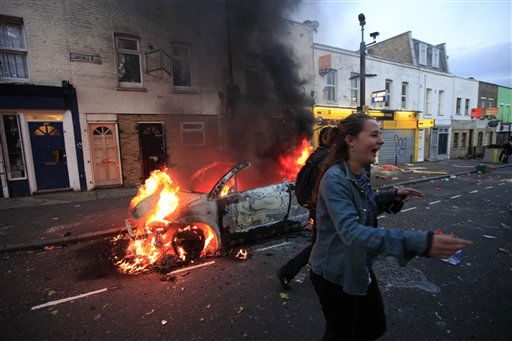 A girl  jokes as a car burns after it was set on fire by rioters in Hackney, east London, Monday Aug. 8, 2011. Youths set fire to shops and vehicles in a host of areas of London _ which will host next summer&#39;s Olympic Games _ and clashed with police in the nation&#39;s central city of Birmingham, as authorities struggled to halt groups of rampaging young people. &#40;AP Photo&#47;Lefteris Pitarakis&#41; <span class=meta>(AP Photo&#47; Lefteris Pitarakis)</span>