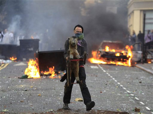 A masked youth carries a toy backdropped by a burning car and garbage bins set on fire by rioters in Hackney, east London, Monday Aug. 8, 2011. Violence and looting spread across some of London&#39;s most impoverished neighborhoods on Monday, with youths setting fire to shops and vehicles, during a third day of rioting in the city that will host next summer&#39;s Olympic Games. &#40;AP Photo&#47;Lefteris Pitarakis&#41; <span class=meta>(AP Photo&#47; Lefteris Pitarakis)</span>