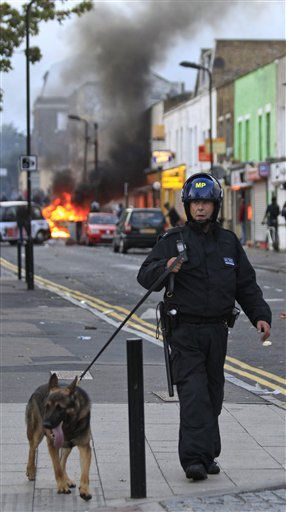 "<div class=""meta ""><span class=""caption-text "">A British police officer walks with a police dog as a car, background, burns after it was set on fire by rioters in Hackney, east London, Monday Aug. 8, 2011. Youths set fire to shops and vehicles in a host of areas of London _ which will host next summer's Olympic Games _ and clashed with police in the nation's central city of Birmingham, as authorities struggled to halt groups of rampaging young people. (AP Photo/Lefteris Pitarakis) (AP Photo/ Lefteris Pitarakis)</span></div>"