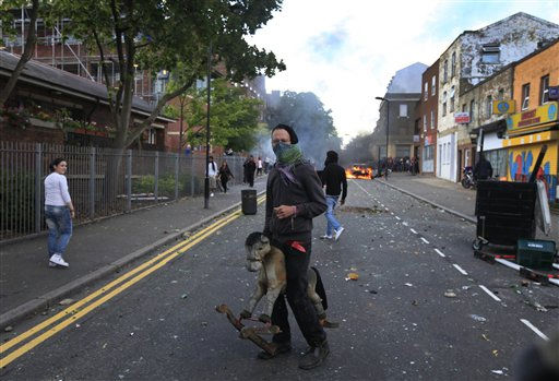A masked youth carries a toy backdropped by a burning car and  garbage bins, set on fire by rioters in Hackney, east London, Monday Aug. 8, 2011. Youths set fire to shops and vehicles in a host of areas of London _ which will host next summer&#39;s Olympic Games _ and clashed with police in the nation&#39;s central city of Birmingham, as authorities struggled to halt groups of rampaging young people.  &#40;AP Photo&#47;Lefteris Pitarakis&#41; <span class=meta>(AP Photo&#47; Lefteris Pitarakis)</span>
