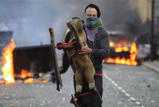 "<div class=""meta ""><span class=""caption-text "">A masked  man carries a toy backdropped by a burning car and  garbage bins set on fire by rioters in Hackney, east London, Monday Aug. 8, 2011. Youths set fire to shops and vehicles in a host of areas of London _ which will host next summer's Olympic Games _ and clashed with police in the nation's central city of Birmingham, as authorities struggled to halt groups of rampaging young people.  (AP Photo/Lefteris Pitarakis) (AP Photo/ Lefteris Pitarakis)</span></div>"