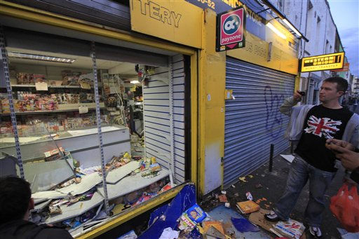 "<div class=""meta ""><span class=""caption-text "">People look on after a shop was attacked by rioters in Hackney, east London, Monday Aug. 8, 2011. Youths set fire to shops and vehicles in a host of areas of London _ which will host next summer's Olympic Games _ and clashed with police in the nation's central city of Birmingham, as authorities struggled to halt groups of rampaging young people. (AP Photo/Lefteris Pitarakis) (AP Photo/ Lefteris Pitarakis)</span></div>"