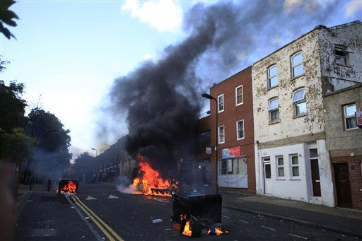 Burning garbage bins are set on fire by rioters in Hackney, east London, Monday Aug. 8, 2011. Youths set fire to shops and vehicles in a host of areas of London _ which will host next summer&#39;s Olympic Games _ and clashed with police in the nation&#39;s central city of Birmingham, as authorities struggled to halt groups of rampaging young people.  &#40;AP Photo&#47;Lefteris Pitarakis&#41; <span class=meta>(AP Photo&#47; Lefteris Pitarakis)</span>