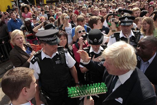 London Mayor Boris Johnson talks with a cleanup volunteer holding a broom, during a visit to meet residents in Clapham, south London, Tuesday Aug. 9, 2011, one of the areas affected by rioting. A wave of violence and looting has raged across London since Saturday, as authorities struggled to contain the country&#39;s worst unrest since race riots set the capital ablaze in the 1980s.  Some 525 arrests have been made in London alone and dozens were arrested in other cities. Police announced Tuesday that plastic bullets would be &#34;one of the tactics&#34; available to officers to quell the riots.&#40;AP Photo&#47;Matt Dunham&#41; <span class=meta>(AP Photo&#47; Matt Dunham)</span>