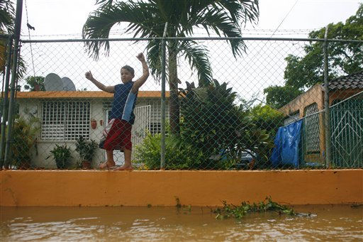 A child walks hanging from a fence outside his flooded house after hurricane Irene hit the area in Naguabo, Puerto Rico, Monday, Aug. 22, 2011.   <span class=meta>(AP Photo&#47; Ricardo Arduengo)</span>
