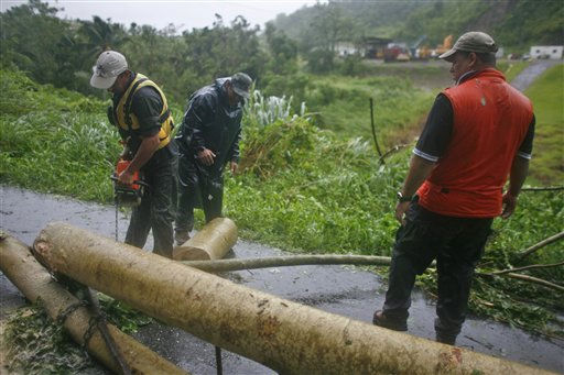 Civil defense workers remove fallen trees from a road after hurricane Irene hit the area in Naguabo, Puerto Rico, Monday, Aug. 22, 2011. Hurricane Irene headed out over warm ocean water on a path that could take it to northeastern Dominican Republic and part of Haiti early Tuesday and to the U.S. mainland by the end of the week.   <span class=meta>(AP Photo&#47; Ricardo Arduengo)</span>