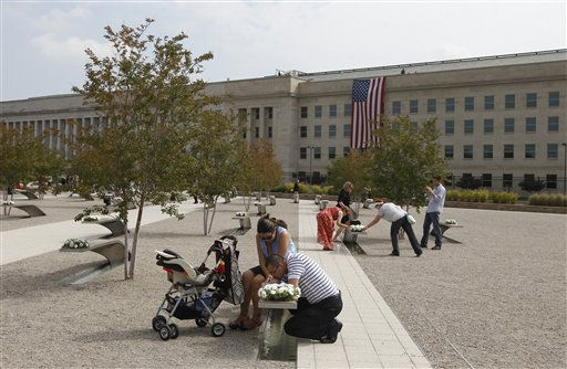 Chin Sok Wells, from McKinney, Texas, kisses his 10-week-old baby Cristian on his wife Cathy&#39;s lap as they gather around the memorial bench of his sister, Army Spc. Chin Sun Pak Wells, who was killed in the Pentagon attacks, as the 10th anniversary of the September 11 attacks are observed at the Pentagon in Washington, Sunday, Sept. 11, 2011.   <span class=meta>(AP Photo&#47; Charles Dharapak)</span>