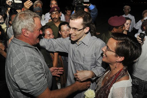 Freed American Shane Bauer, center, meets his father Al Bauer as his fiance Sarah Shourd looks on upon his arrival from Iran, in Muscat, Oman Wednesday, Sept. 21, 2011. After more than two years in Iranian custody, two Americans convicted as spies took their first steps toward home Wednesday as they bounded down from a private jet and into the arms of family for a joyful reunion in the Gulf state of Oman. &#40;AP Photo&#47;Sultan Al-Hasani&#41; <span class=meta>(AP Photo&#47; Sultan Al-Hasani)</span>