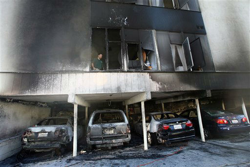 An investigator works the scene where fire caused damage to a two-story apartment at 1156 N. Cahuenga Blvd. in Hollywood, section of Los Angeles, on Friday, Dec. 30, 2011. An arsonist torched car after car early Friday, sending firefighters scrambling to put out more than a dozen blazes in Hollywood and neighboring West Hollywood. &#40;AP Photo&#47;Ringo H.W. Chiu&#41; <span class=meta>(AP Photo&#47; Ringo H.W. Chiu)</span>