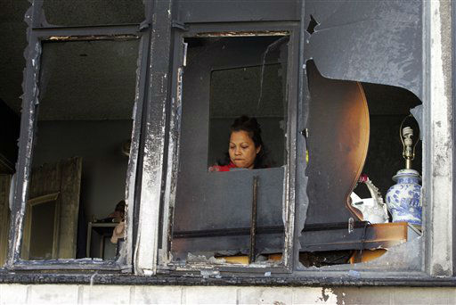 "<div class=""meta ""><span class=""caption-text "">Suyapa Herrera returns to her home where fire caused damage to a two-story apartment on N. Cahuenga Boulevard in the Hollywood section of Los Angeles, on Friday, Dec. 30, 2011. An arsonist torched car after car early Friday, sending firefighters scrambling to put out more than a dozen blazes in Hollywood and neighboring West Hollywood. (AP Photo/Ringo H.W. Chiu) (AP Photo/ Ringo H.W. Chiu)</span></div>"