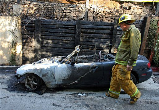 Los Angeles City firefighter Dane Jackson investigates the scene where fire caused damage to a home once occupied by Doors frontman Jim Morrison, at 8021 Rothdell Trail in the Hollywood Hills, section of Los Angeles, on Friday, Dec. 30, 2011. An arsonist torched car after car early Friday, sending firefighters scrambling to put out more than a dozen blazes in Hollywood and neighboring West Hollywood. &#40;AP Photo&#47;Ringo H.W. Chiu&#41; <span class=meta>(AP Photo&#47; Ringo H.W. Chiu)</span>