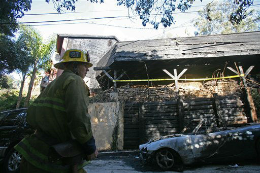 "<div class=""meta ""><span class=""caption-text "">Los Angeles City firefighter Dane Jackson investigates the scene where fire caused damage to a home once occupied by Doors frontman Jim Morrison, at 8021 Rothdell Trail in the Hollywood Hills, section of Los Angeles, on Friday, Dec. 30, 2011. An arsonist torched car after car early Friday, sending firefighters scrambling to put out more than a dozen blazes in Hollywood and neighboring West Hollywood. (AP Photo/Ringo H.W. Chiu) (AP Photo/ Ringo H.W. Chiu)</span></div>"