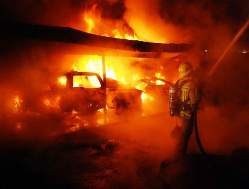 A Los Angeles Fire Department firefighter is shown at a fire in West Hollywood, Calif., on Friday Dec.30, 2011. An arsonist torched car after car early Friday, sending firefighters scrambling to put out more than a dozen blazes in Hollywood and neighboring West Hollywood. The fires started shortly after midnight and occurred over a four-hour span before dawn. &#40;AP Photo&#47;Mike Meadows&#41; <span class=meta>(AP Photo&#47; Mike Meadows)</span>