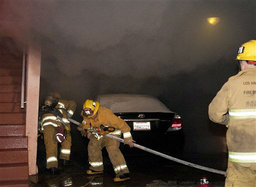 Los Angeles Fire Department firefighters extinguish a car on fire in a carport in the Sherman Oaks neighborhood of Los Angeles on Monday, Jan. 2, 2012. For the fifth night in a row, a spate of arson fires has sent firefighters scrambling to extinguish car fires in the Hollywood, Hollywood Hills, Studio City, and Sherman Oaks neighborhoods of Los Angeles. The Los Angeles Fire Department confirms a person of interest has been detained and is being questioned in connection with the arson spree. &#40;AP Photo&#47;Dan Steinberg&#41; <span class=meta>(AP Photo&#47; DAN STEINBERG)</span>