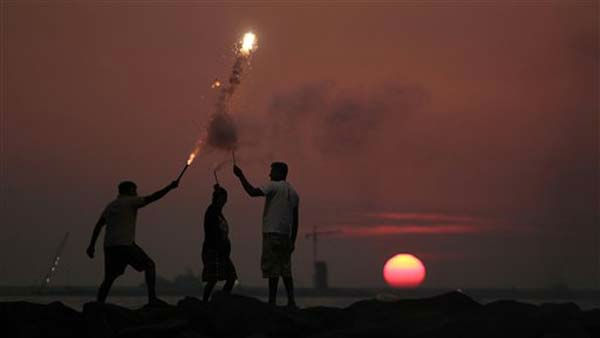 Young Sri Lankan boys play with firecrackers on the eve of the New Year, as the sun sets in Colombo, Sri Lanka, Saturday, Dec. 31, 2011. &#40;AP Photo&#47; Eranga Jayawardena&#41; <span class=meta>(AP Photo&#47; Eranga Jayawardena)</span>