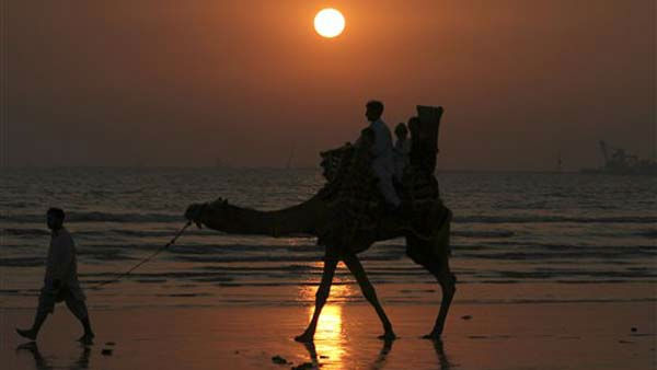 Pakistani youth enjoy a camel ride as the sun sets in Karachi, Pakistan on Saturday, Dec. 31, 2011. &#40;AP Photo&#47;Fareed Khan&#41; <span class=meta>(AP Photo&#47; Fareed Khan)</span>